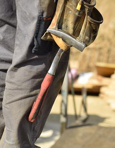 Nahaufnahme eines Hammers am Werkzeuggürtels eines Bauarbeiters